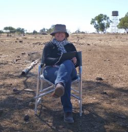 A photo of Christine Porter, painting on site in the Australian landscape - dry earth , high tank in the distance.