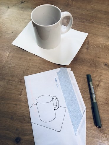 a photo of a white cup on a piece of white paper, on a desk. Also on the desk is an envelope with a line drawing of the cup, with the pen that it was drawn with next to it.