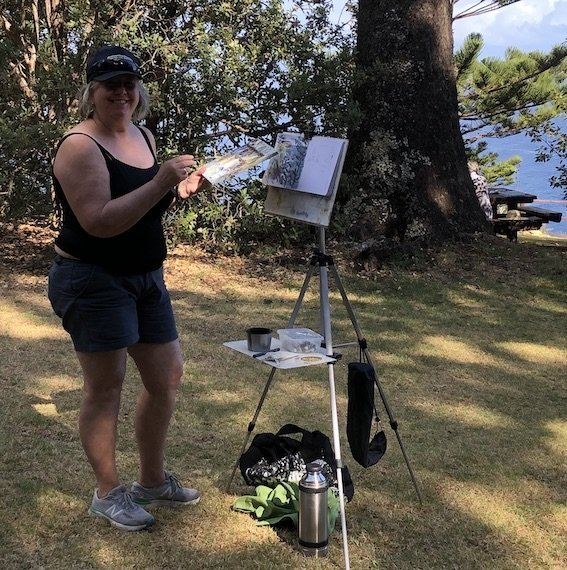 photo of Christine Porter standing at an easel at the Captan Cook lookout painting. She's wearing short, singlet, running shoes and a cap.