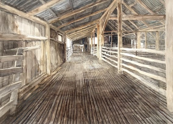 A painting of a shearing shed interior by Christine Porter, entitled With Skylight, looking west. It shows a long alleyway, with strong linear perspective on the flooboards going towards a gate in the distance. Across the rails, the rest of the shed is visible and a skylight, out of the picture, casts light across the floor.