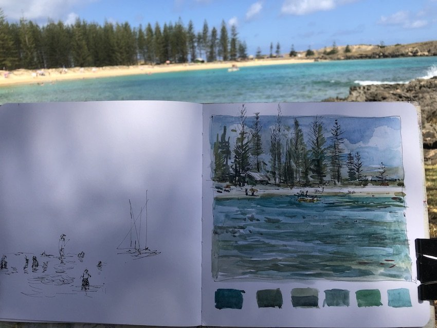 a photo of a sketchbook and a blue watered bay with white sands and norfolk island pines. The sketchbook, in dappled light, shows the drawing by Christine Porter, of that scene