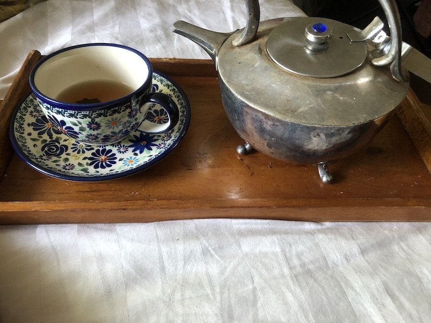 a photo of a silver plated tea pot and a patterned cup and saucer on a wooden tray on a counterpane.