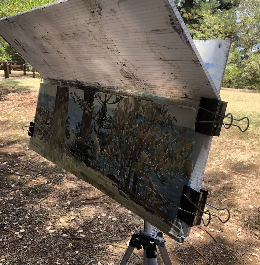 a photo of an easel out in the field. With a piece of ripple board shading the page.