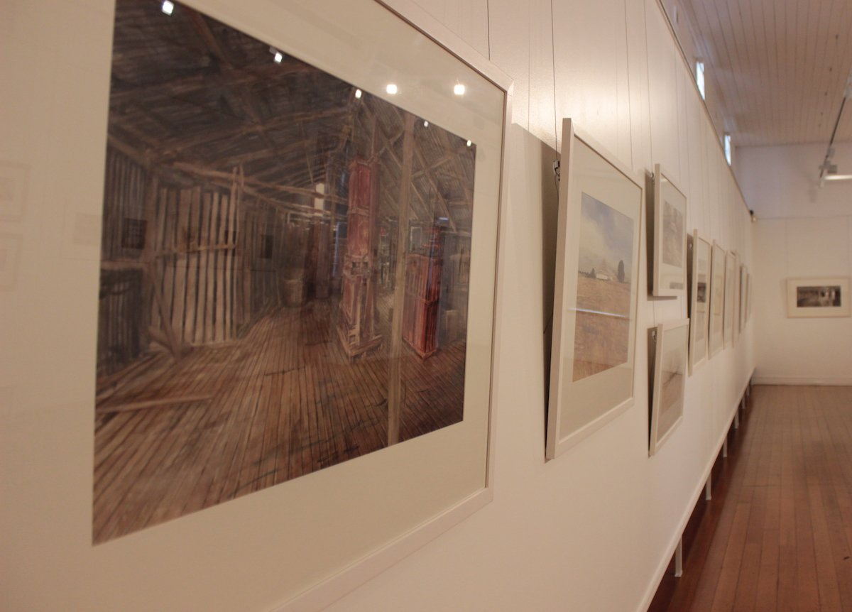 Photo of Christine Porter's exhibition at the Gympie Regional Gallery in March2020, showing a large painting of the interior of a shearing shed, and other paintings off into the distance.