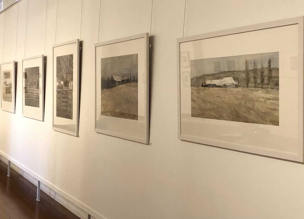 Photo of Christine Porter's exhibition at the Gympie Regional Gallery in March2020, showing a large painting of shearing shed, and other paintings off into the distance. a