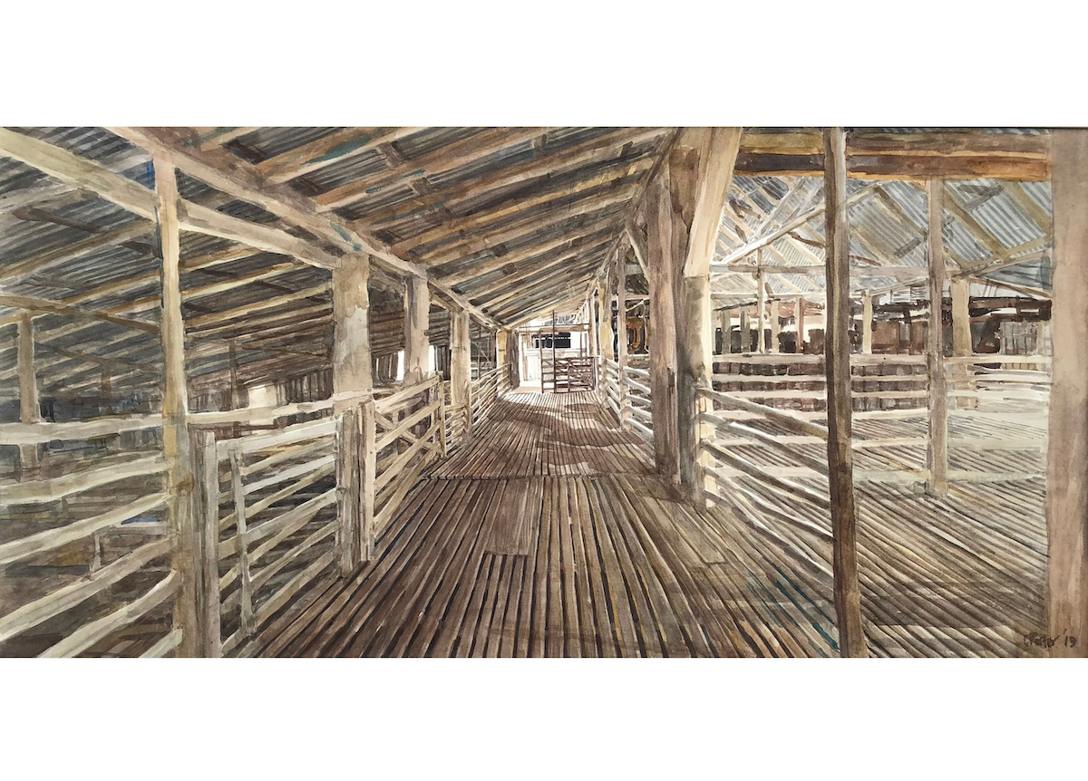 "Watercolour painting by Christine Porter of the shearing shed at ""Boorolong"" near Armidale showing the interior of the shed with the focus being a patch of sunlight coming onto the timber floor in the main pen area. In this painting we see the slotted floor, timber beams going off into the distance"