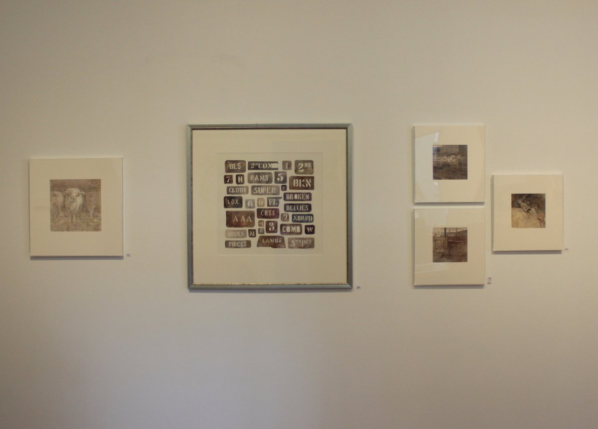 Photo of Christine Porter's exhibition at the Gympie Regional Gallery in March2020, showing a large painting of a collection of woolstencils as well as a few other small paintings installed.