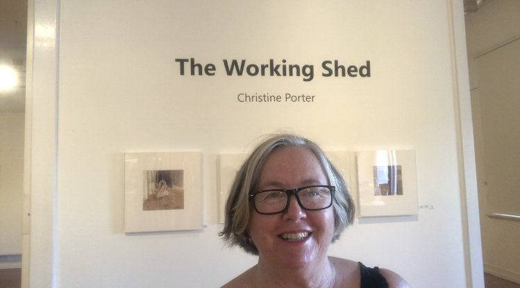 "A photo of Christine Porter standing in front of the first wall of her exhibition in Gympie in March2020. The text on the wall above her head says ""the Working Shed"" ""Christine Porter"" and there are two of the four paintings below, visible."