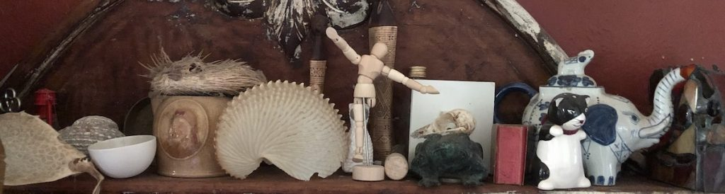 a Photo of a shelf with lots of toys and objects on it. Including an articulated artist's toy, a china elephant teapot, a jug, a big shell.
