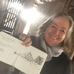 A photo of Christine Porter holding up a sketchbook of the shearing shed she appears to be standing in. A big smile